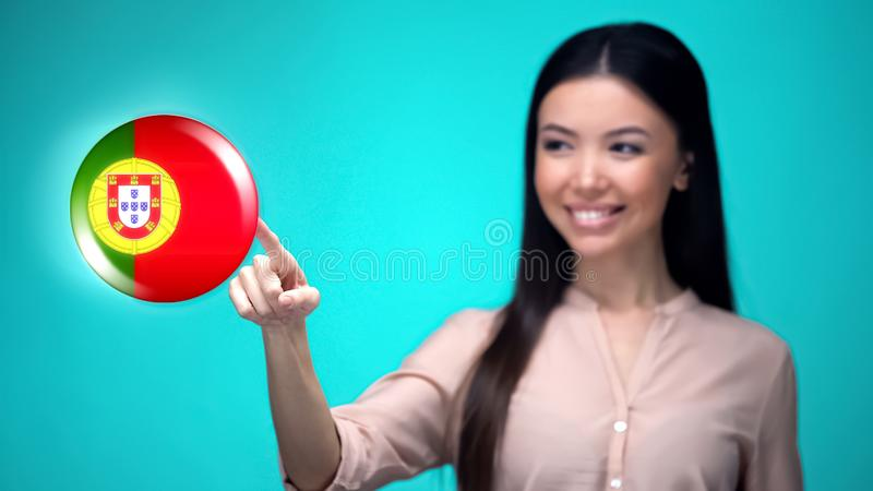 Beautiful female pushing Portuguese flag button, ready to learn foreign language. Stock photo royalty free stock photo