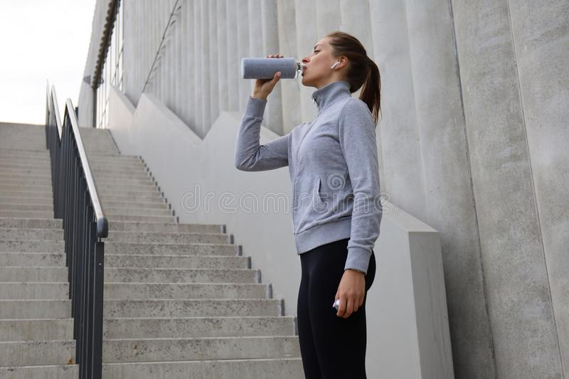 Beautiful female runner standing outdoors, drinking water from bottle. Fitness woman takes a break after running workout royalty free stock image