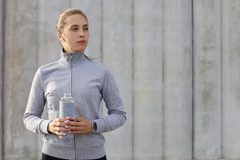 Beautiful female runner is standing outdoors holding water bottle. Fitness woman takes a break after running workout stock photography