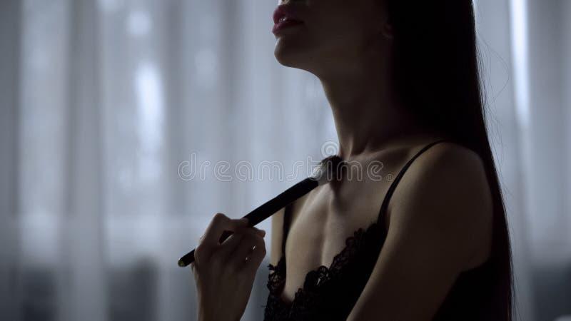 Beautiful female seductively brushes skin with cosmetics tool, flirting gestures royalty free stock photo