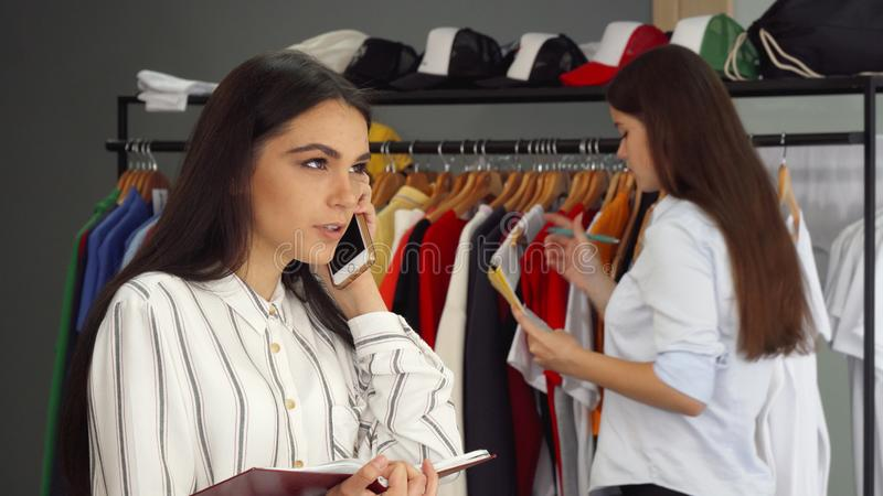 Beautiful female shop assistant talking on the phone, working at the clothing store royalty free stock photos