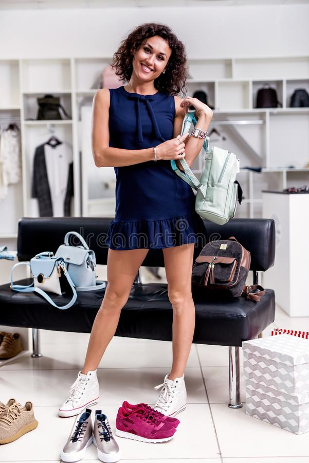Beautiful female shopper standing looking back at camera in new short dress holding backpack wearing sneakers surrounded. By variety of shoes and bags in royalty free stock image