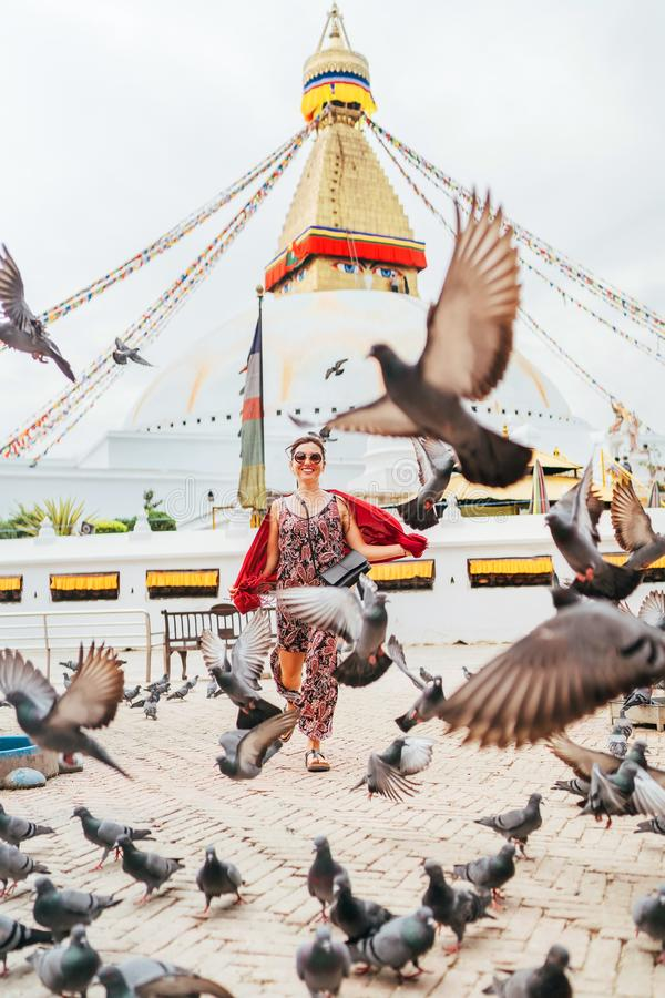 Beautiful female sincerely smiling and going by square through pigeons flock with Boudhanath Stupa - the largest spherical stupas. Beautiful female sincere royalty free stock photos