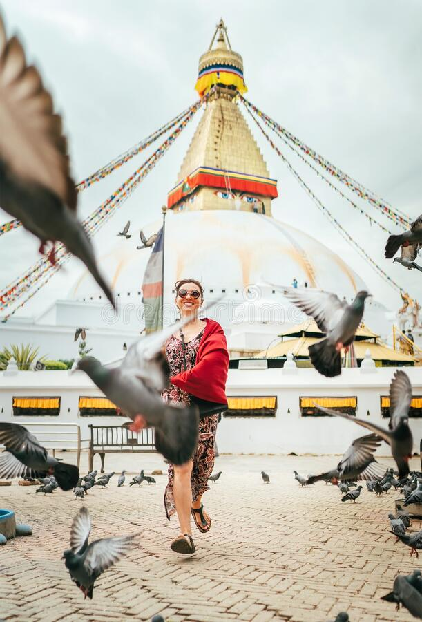 Beautiful female sincerely smiling and going by square through pigeons flock with Boudhanath Stupa - the largest spherical stupas. In Nepal. Traveling around stock image