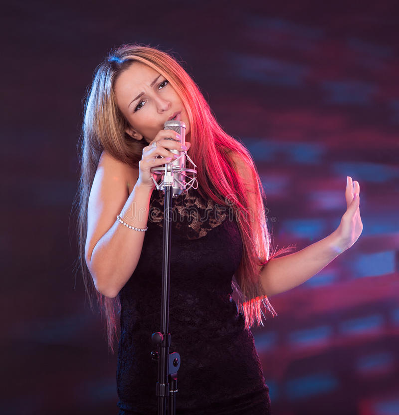 Beautiful female singer. With a microphone on white stock photography
