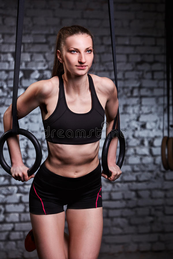 Beautiful female sporty woman using rings equipment in cross fit gym against brick wall. royalty free stock images