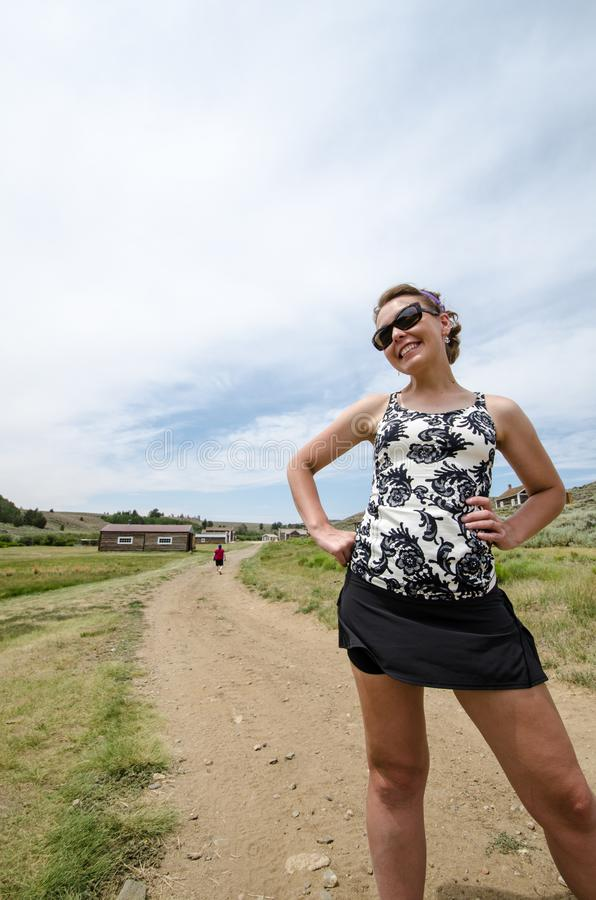 Beautiful female stands and poses by a dirt road in Wyoming at S. Outh Pass City, clouds and blue sky stock photo