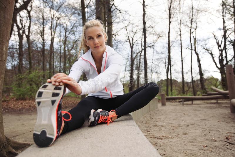 Beautiful female stretching before running. Beautiful young fitness female stretching before running in park. Caucasian woman exercising in nature royalty free stock image