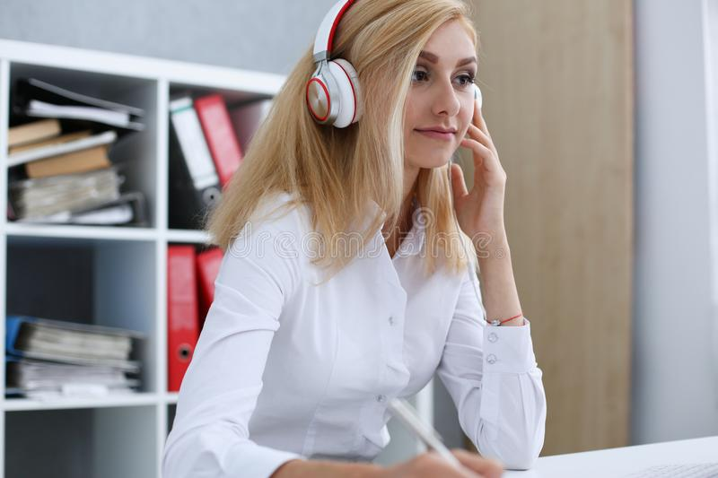 Beautiful female student with headphones listening to music stock images