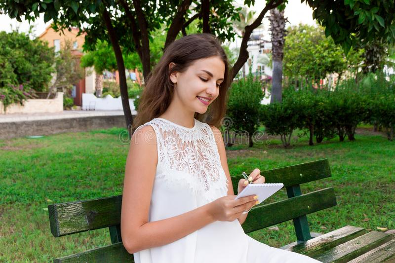 Beautiful female student is writing her ideas and thoughts into the notebook sitting on the bench in the park stock photos