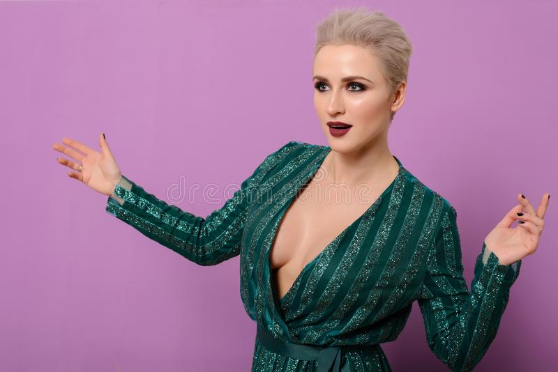 Beautiful female Swede of middle age with short-cut blond hair and green evening dress positively poses with arms outstretched royalty free stock photography