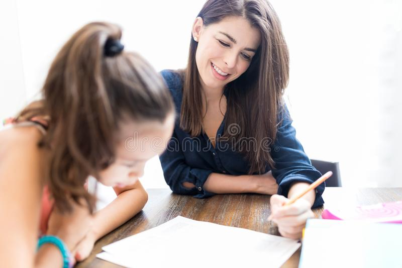 Teacher Smiling While Teaching Girl At Home royalty free stock image