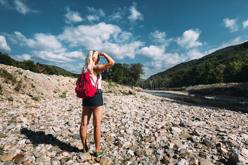 Beautiful Female Tourist Stands On River Bank And Enjoys View Of Mountains In Summer stock photos
