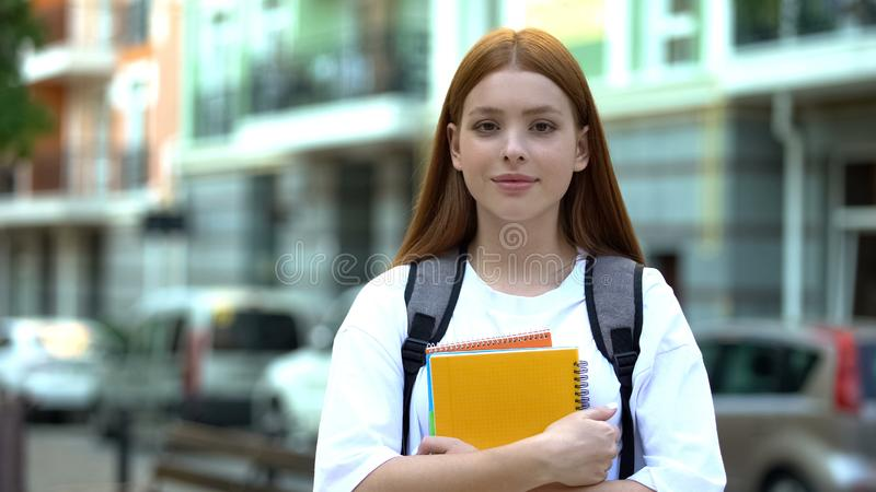 Beautiful female university student with backpack holding copybooks in big city. Stock photo stock photography