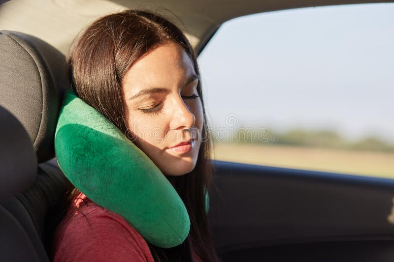 Beautiful female uses neck pillow for sleeping in car, has trip on long distance, trries to relax, feels pain in neck for being in royalty free stock images