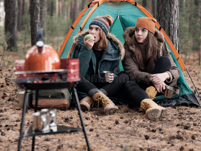 Beautiful females relaxing in tent while camping royalty free stock images