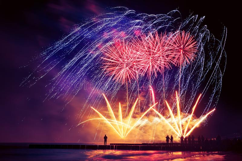 Beautiful, festive, colorful fireworks over the sea with reflection stock image