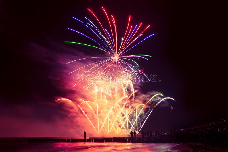 Beautiful, festive, colorful fireworks over the sea with reflection royalty free stock image