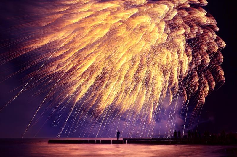 Beautiful, festive, fireworks like a golden rain over the sea wi. Th reflection and little silhouette of a man. Very long shutter speed stock image