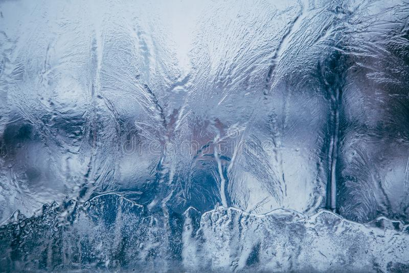 Beautiful festive frosty pattern on a blue background on glass royalty free stock images