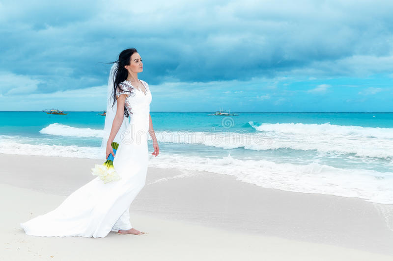 Beautiful fiancee in white wedding dress with big long white train and with wedding bouquet stand on shore sea.  stock photo