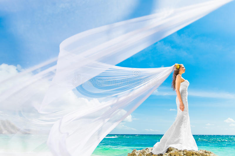 beautiful fiancee in white wedding dress and big long white train, stand on shore sea stock photography