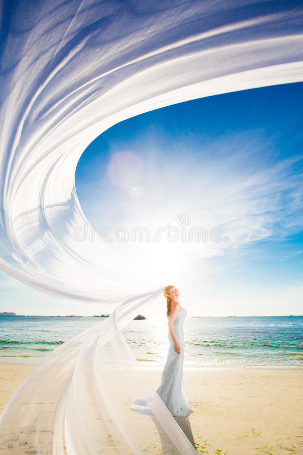 beautiful fiancee in white wedding dress and big long white train, stand on shore sea at sunset royalty free stock photo