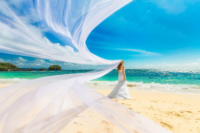 beautiful fiancee in white wedding dress and big long white train, stand on shore sea at sunset stock images
