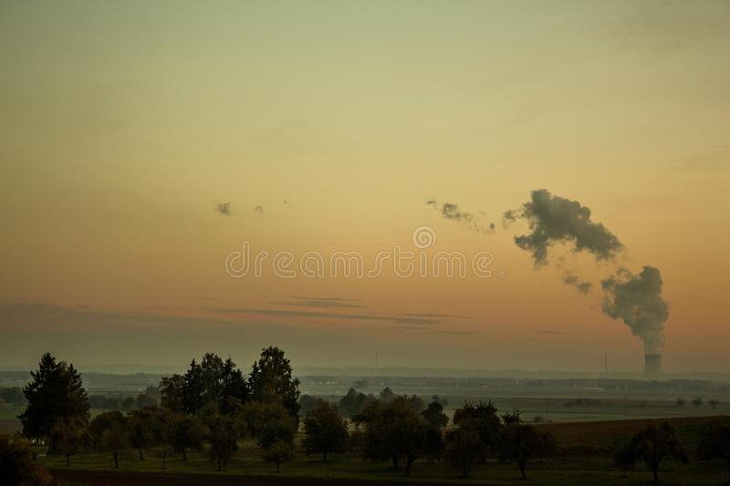 Beautiful field with trees with a nuclear station in the background. Global Warming stock images