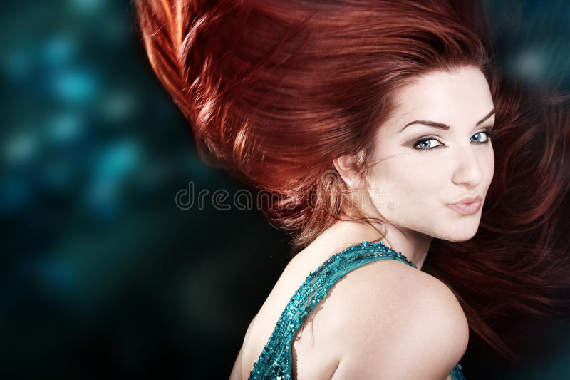 Beautiful fiery redhead. A beautiful fiery redhaired woman with her hair mid movement with a blue abstract background royalty free stock images