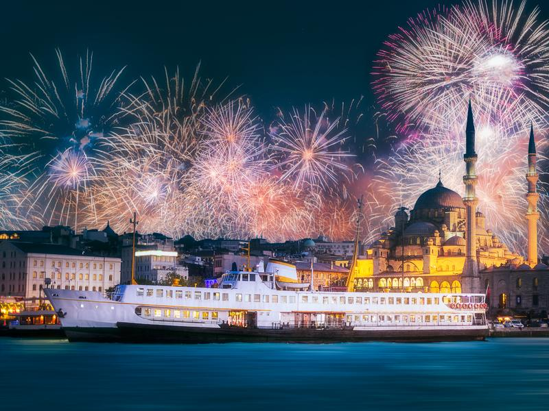 Beautiful fireworks above public ferry and old district of Istanbul. Beautiful fireworks above pier, public ferry and old district of Istanbul with Mosque on royalty free stock image