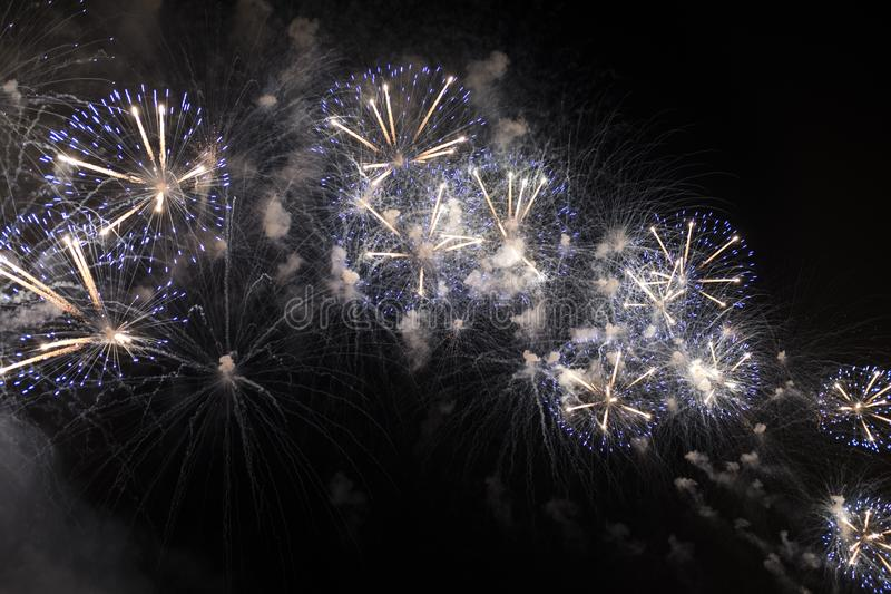 Multiple Fireworks in night sky in a composition in shades blue and white stock photos