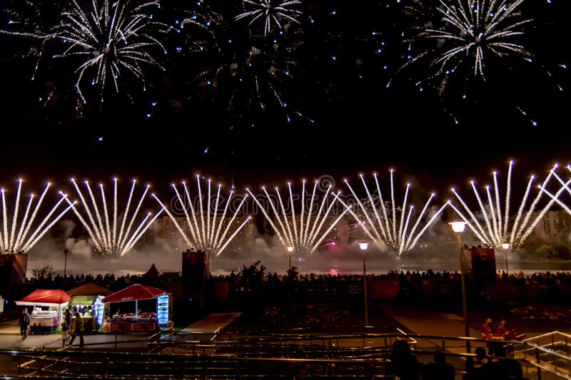 Beautiful fireworks in the night city. Fan volleys. Bright flash, grand fireworks display. Copy space stock photography