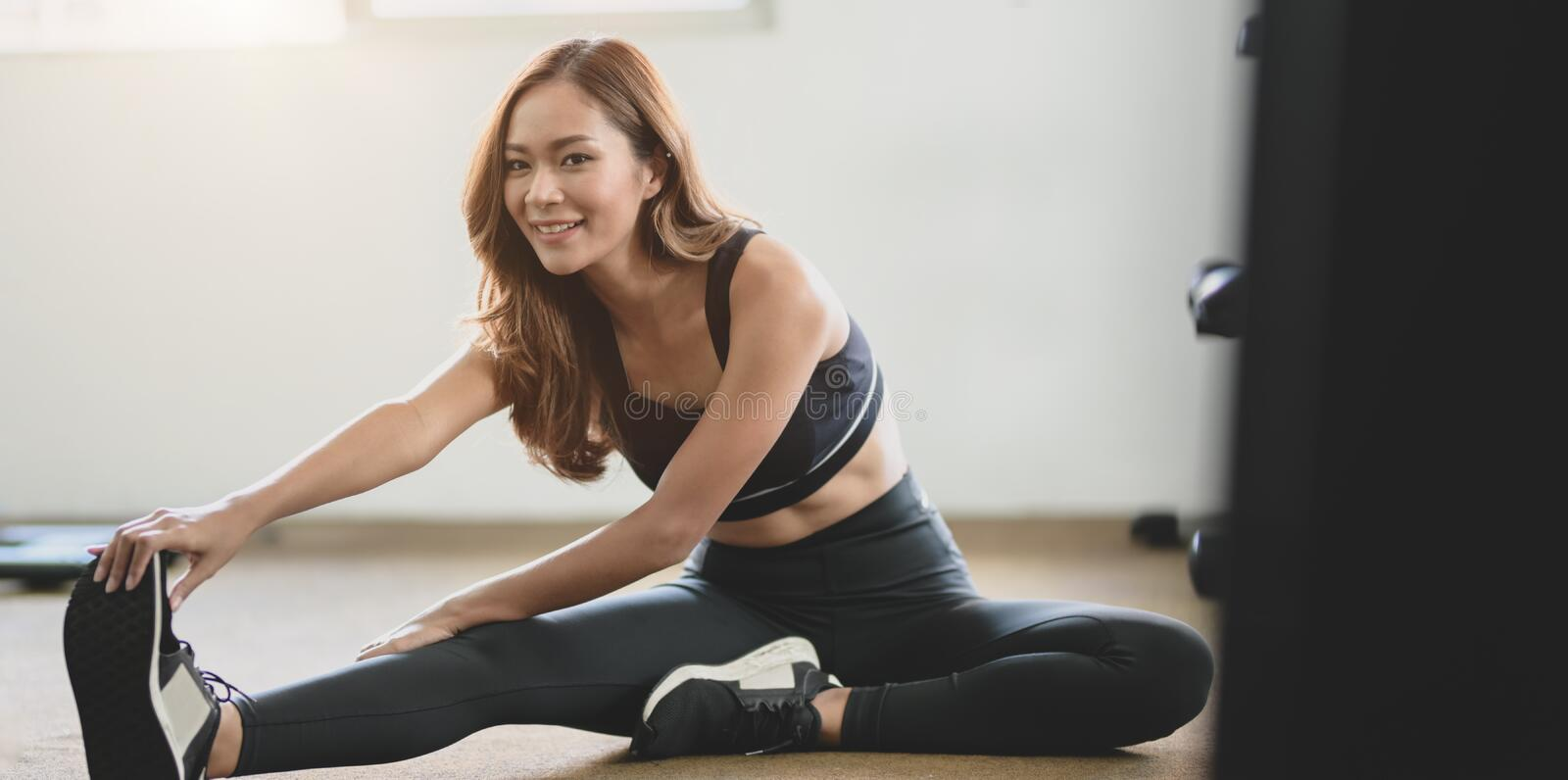Beautiful fit Asian woman with tan and slim body stretching legs before exercise royalty free stock image