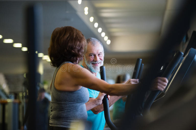 Beautiful fit senior couple in gym doing cardio work out. stock photography