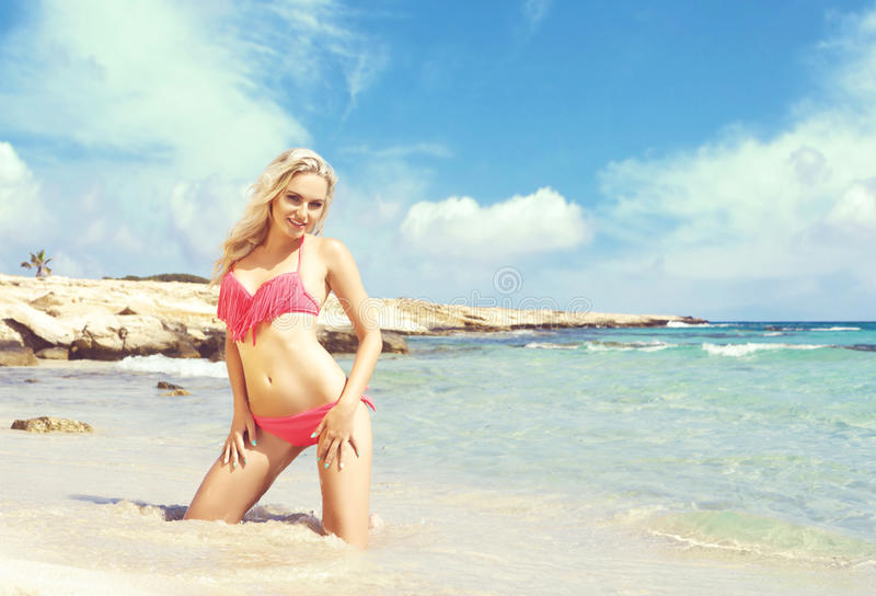 Beautiful, fit and girl in pink swimsuit posing on a beach royalty free stock image