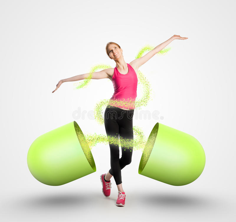 Beautiful fit woman and a giant capsule royalty free stock images