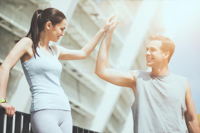 Beautiful fit woman high fives a handsome athletic man. stock images