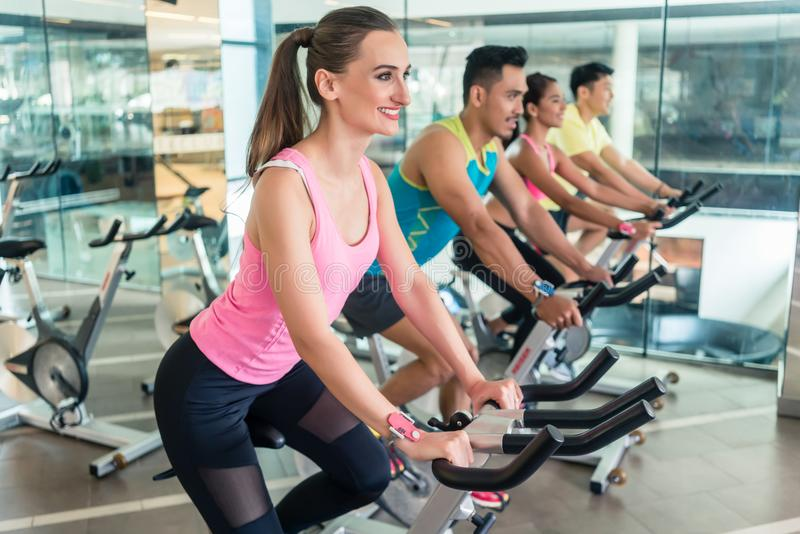 Beautiful fit woman smiling during cardio workout at indoor cycling class royalty free stock images