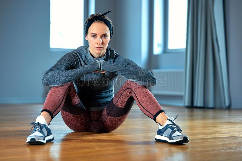 Beautiful fit woman in sportswear posing while sitting on the floor in front of window at gym stock photography
