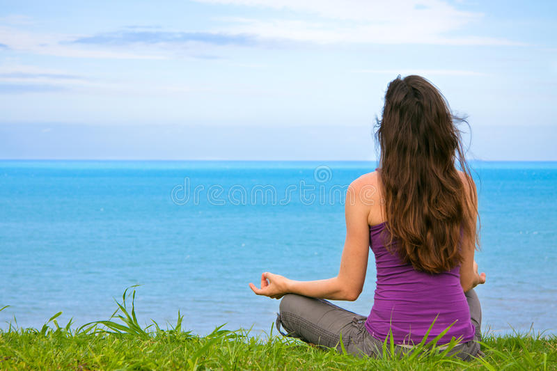 Beautiful fit young woman meditating outdoors stock images