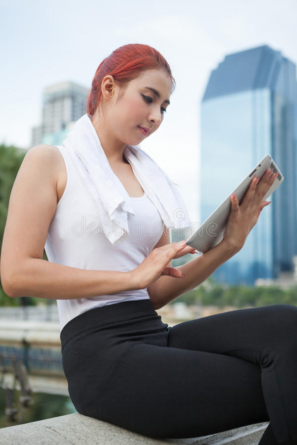 Beautiful fitness asian woman with tablet stock images