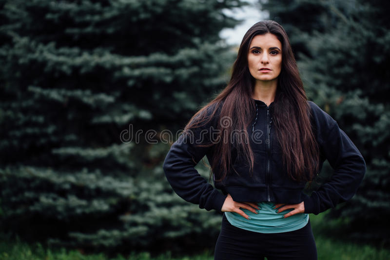 Beautiful fitness brunette athlete woman resting posing after work out exercising at park. Beautiful fitness athlete woman resting posing after work out stock photos