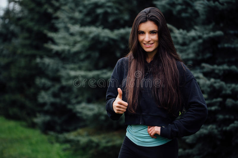 Beautiful fitness brunette athlete woman resting posing after work out exercising at park. Beautiful fitness athlete woman resting posing after work out royalty free stock photos