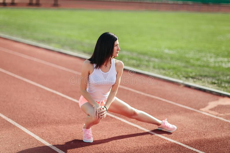 Beautiful fitness brunette girl in shorts and tank top and sneakers does a stretching exercise on the running track at the stadium stock photography