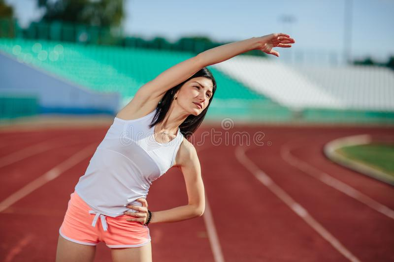 Beautiful fitness brunette girl in in shorts and tank top and sneakers does a stretching exercise on the running track at the royalty free stock image