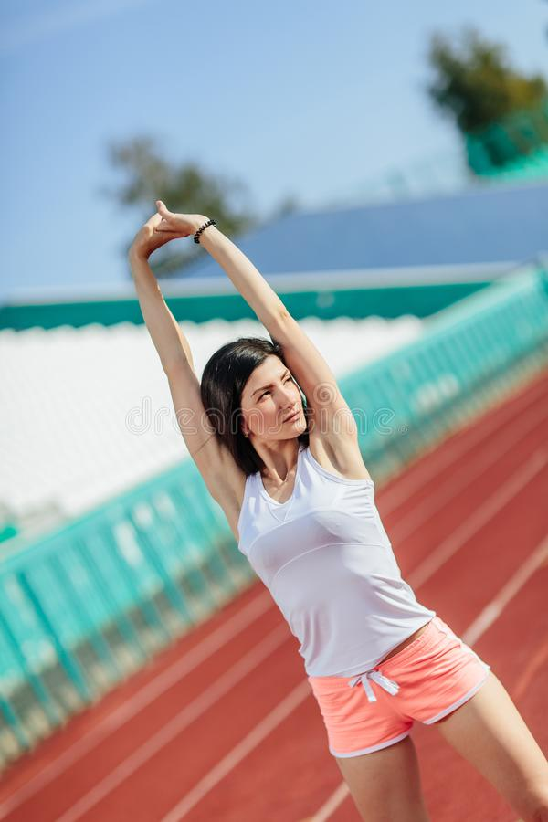 Beautiful fitness brunette girl in in shorts and tank top and sneakers does a stretching exercise on the running track at the stock image