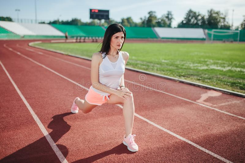 Beautiful fitness brunette girl in in shorts and tank top and sneakers does a stretching exercise on the running track at the stock photography