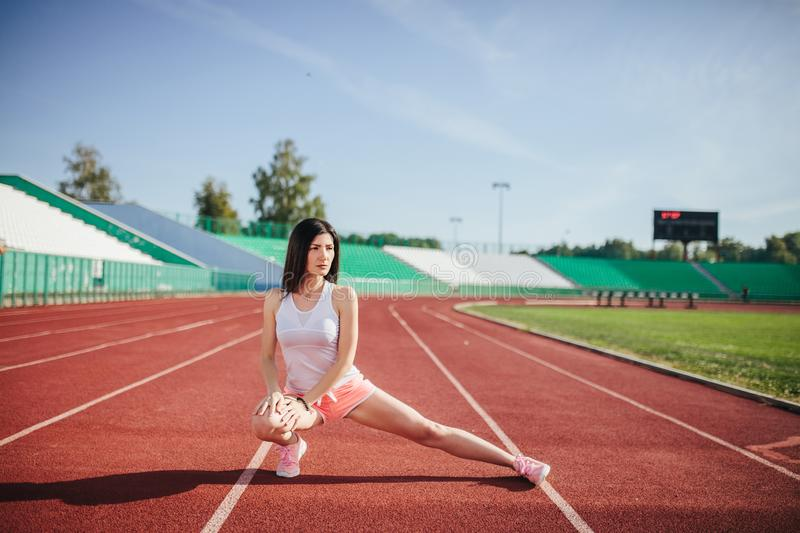 Beautiful fitness brunette girl in sportswear and sneakers does a stretching exercise on the running track at the stadium outdoors stock photos