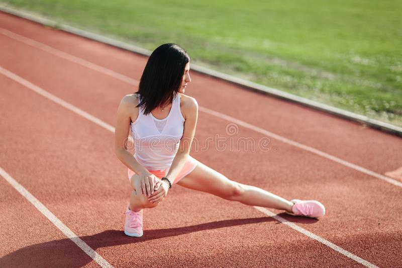 Beautiful fitness brunette girl in sportswear and sneakers does a stretching exercise on the running track at the stadium outdoors stock images
